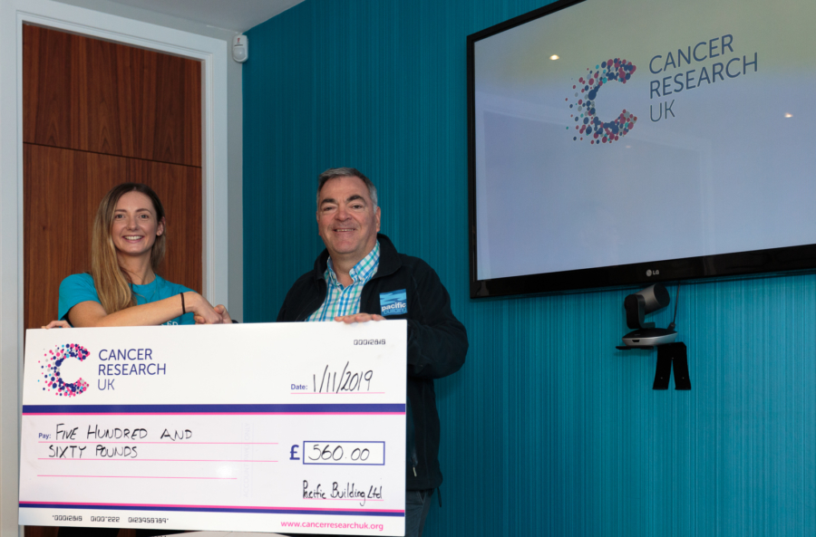 Katie Allan of Cancer Research UK with Brian Gallacher, MD of Pacific Building, holding a cheque for £560